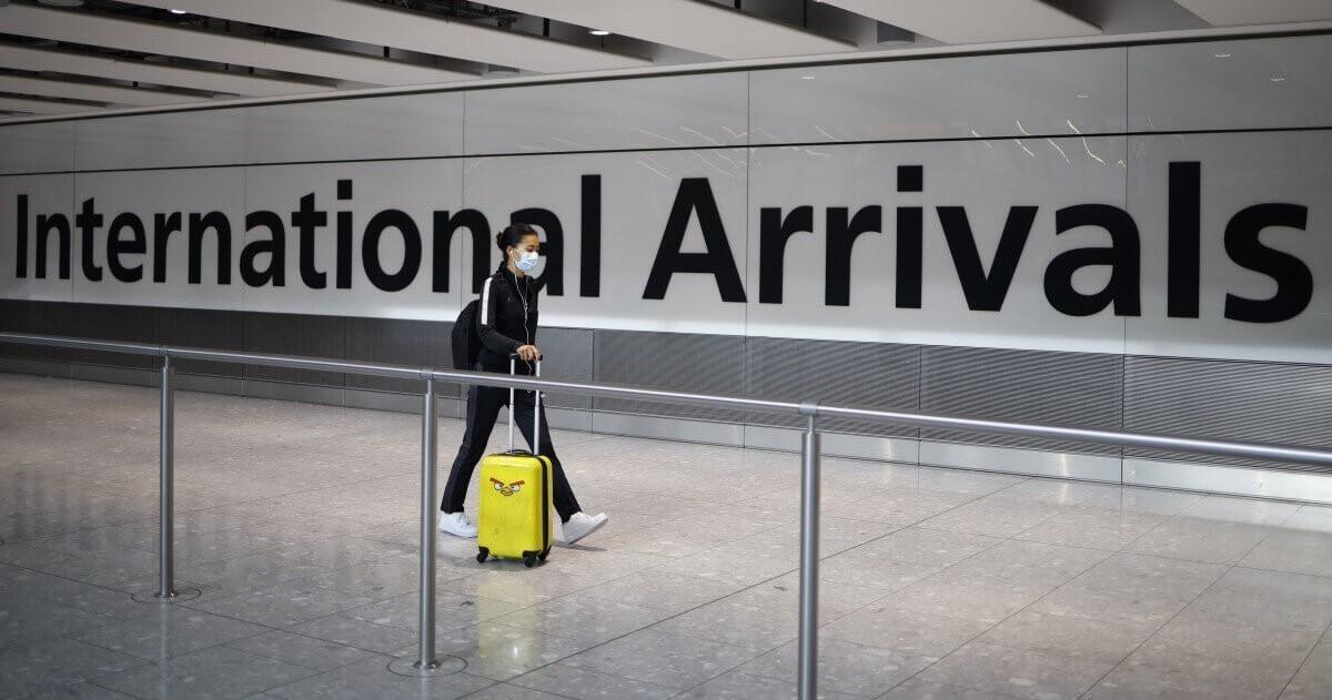Một hành khách đeo khẩu trang để đề phòng virus corona tại sân bay Heathrow, London - Ảnh: Tolga Akmen/AFP